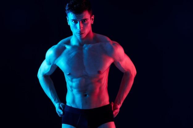 반바지에 섹시한 남자 운동 선수는 검은 배경에 그의 벨트에 손을 보유