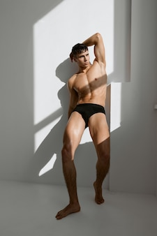 Sexy man in black panties with a pumped body near the window