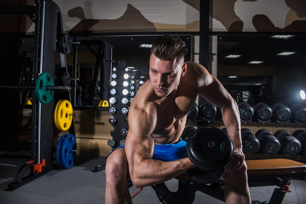 Sexy man in the gym with dumbbells. sporty man