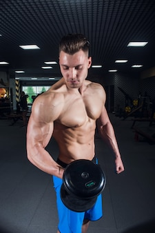 Sexy man in the gym with dumbbells