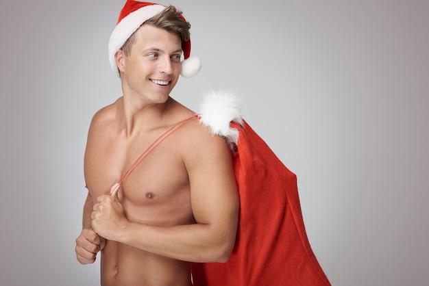 Сексуальный мужчина держит мешок санта-клауса