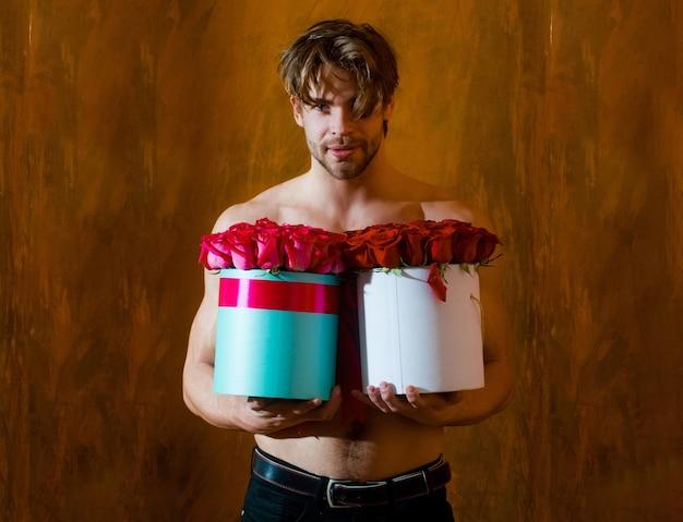 セクシーな男は赤いバラの箱を保持しますセクシュアリティの雰囲気の中で花を持つ若いハンサムな男
