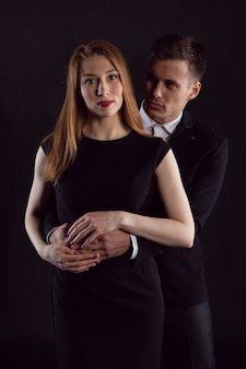 Сексуальный мужчина обнимает очаровательную рыжеволосую женщину сзади