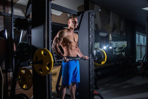 ダンベルとジムでセクシーな男。大きな筋肉とジムでの幅広いバックトレイン、フィットネス、そして腹部の圧迫感を備えたスポーティな男性