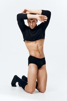 短いtシャツのパンティーと靴下でセクシーな男が胴体ストリップモデルのポーズをポンプアップ