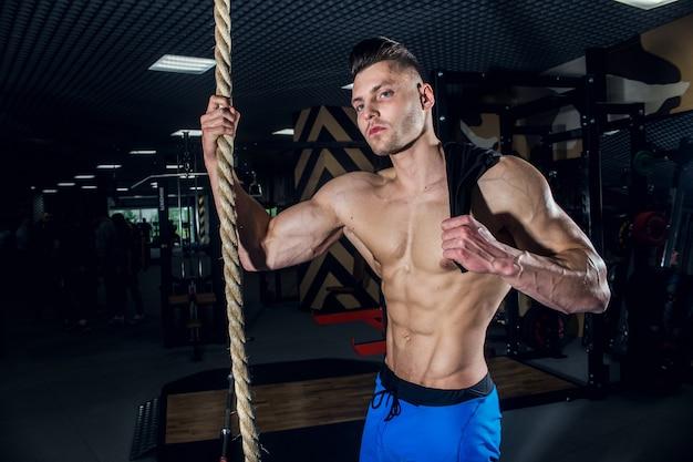 ダンベルとジムでセクシーな男。大きな筋肉とジムでの幅広い背中の列車、フィットネス、そして腹部の圧迫感を備えたスポーティな男性。ロシア、スヴェルドロフスク、2018年6月2日