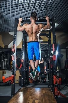 아령과 체육관에서 섹시 한 남자입니다. 큰 근육과 넓은 등을 가진 스포티한 남자는 체육관, 피트니스 및 펌핑된 복부 프레스에서 훈련합니다. 러시아, 스베르들로프스크, 2018년 6월 2일