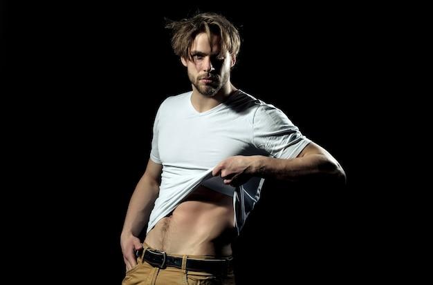 섹시하고 근육질의 몸통을 보여주는 흰색 tshirt의 섹시한 남자