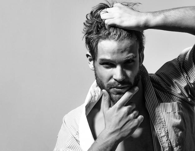 섹시한 남자 또는 단추를 벗긴 셔츠에 근육질의 남자가 머리카락과 수염을 만집니다.