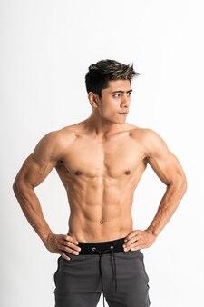 セクシーな男が前を向いて腰スタンドに両手で筋肉の体を見せて、側を見て
