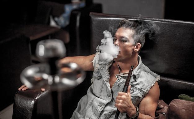 Сексуальный мужчина курит ароматный восточный кальян в ночном клубе.