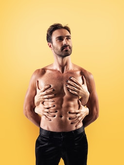 Sexy man touched by multiple woman hands on yellow background