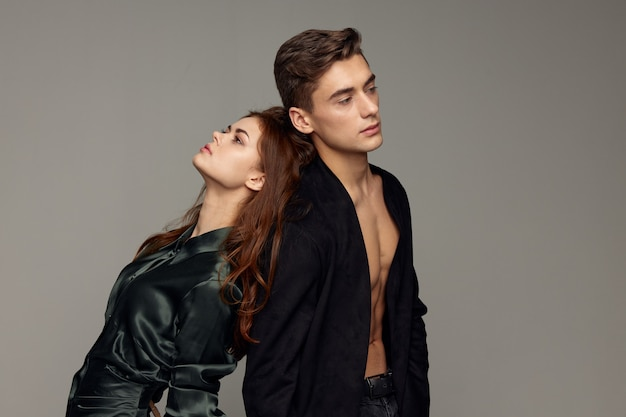 A sexy man in an unbuttoned shirt and a woman in an evening dress stand with their backs to each other.