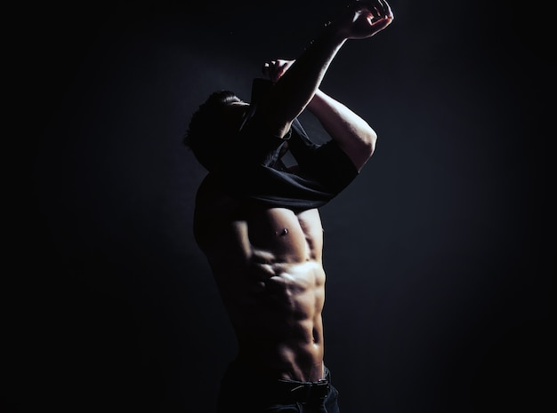 벌거 벗은 근육질의 몸통과 아름다운 몸매로 옷을 벗고 섹시한 남자가 검은 셔츠를 벗다.