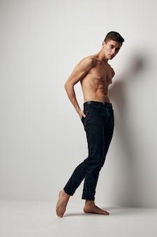 벗은 몸통과 밝은 배경에 바지를 입은 섹시한 남자. 고품질 사진