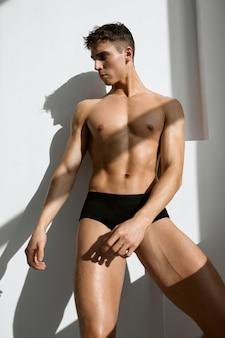 Сексуальный мужчина с накачанным мускулистым телом в темных трусиках на светлом фоне