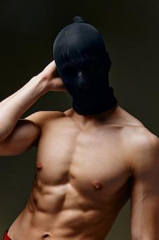 Сексуальный мужчина с накачанным торсом бодибилдер фитнес темный фон и черная маска на голове