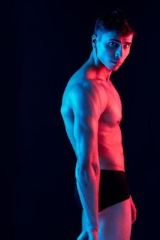 Сексуальный мужчина с накачанным торсом позирует на темном фоне, вид сбоку и неоновый свет