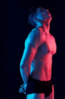 Сексуальный мужчина с накачанным торсом позирует на темном фоне, вид сбоку