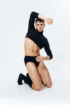 Сексуальный мужчина спортивного телосложения стоит на коленях на светлом фоне