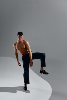 Sexy man with a naked torso in jeans and shoes on a gray background with a raised leg