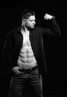 Sexy man with strong abs and chest. athletic man with unbuttoned dark shirt. dark background. pumping muscles. black and white.