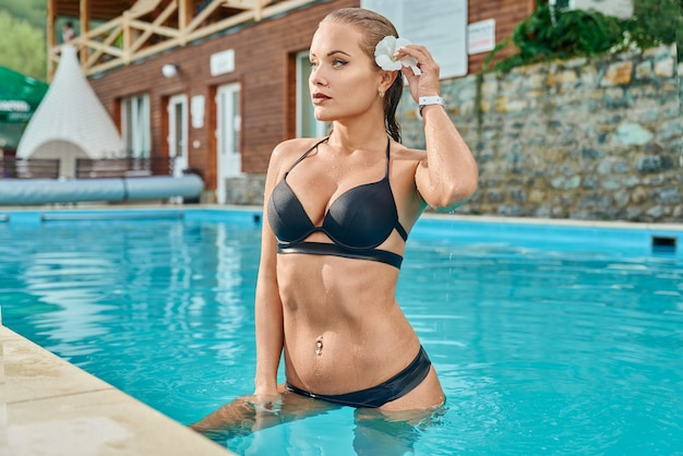 Sexy model on background of pool at spa resort