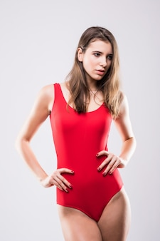 흰색 배경에 고립 된 빨간색 수영 스위트에서 섹시 모델 소녀