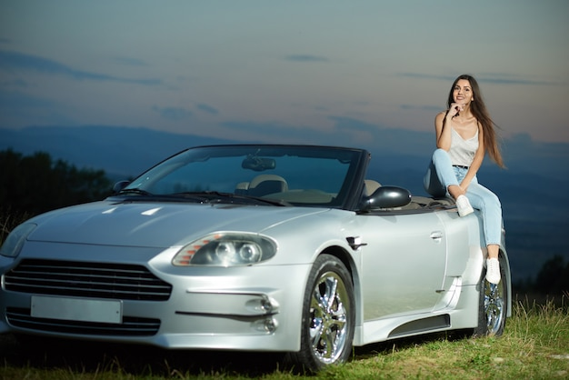 Sexy model posing on luxurious silver cabriolet.
