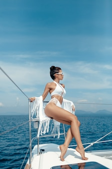 Sexy model in white swimsuit and cape sitting on edge of luxury yacht