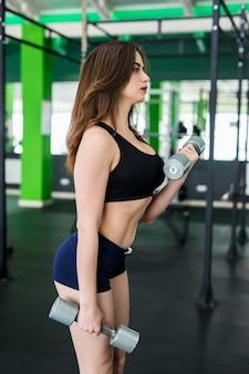 ブルネットの髪を持つセクシーなモデルは黒いスポーツウェアで着飾ったスポーツクラブで演習を行っています