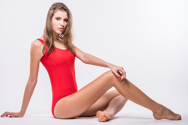 Sexy model with brunette hair is sitting on the floor dressed up in red swimming suit isolated on white background