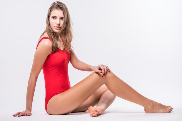 갈색 머리를 가진 섹시한 모델은 흰색 배경에 고립 된 빨간색 수영복을 입고 바닥에 앉아있다