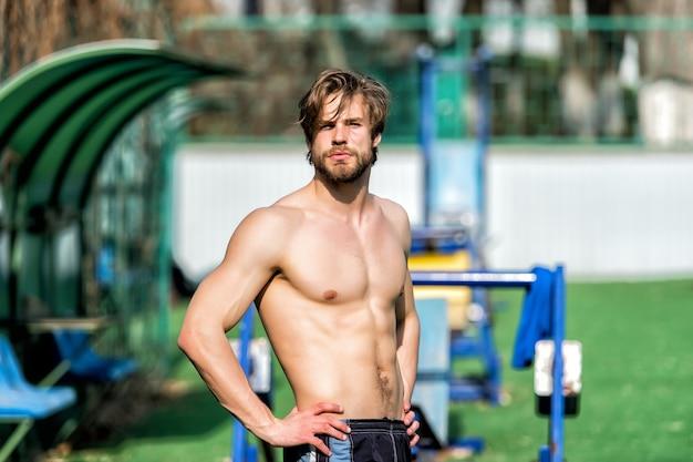 Сексуальный мускулистый парень, бородатый мужчина со стильными волосами и спортивным телом расслабляется на открытом стадионе на размытом фоне. летняя активность и спорт. здоровый образ жизни