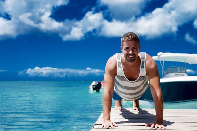海岸で腕立て伏せをしているセクシーな筋肉男。美しい晴れた夏の日。