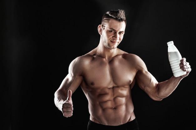 섹시한 근육질 남성 몸통과 잘 생긴 사나이 남자 또는 운동 선수 남자 운동 또는 훈련의 몸, 검은 공간에 음료와 함께 흰색 열 찻잔, 병 또는 플라스크 보유