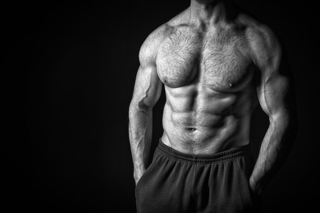 Sexy muscular male torso and body with hairy chest of handsome macho man or athlete guy workout or training, black and white