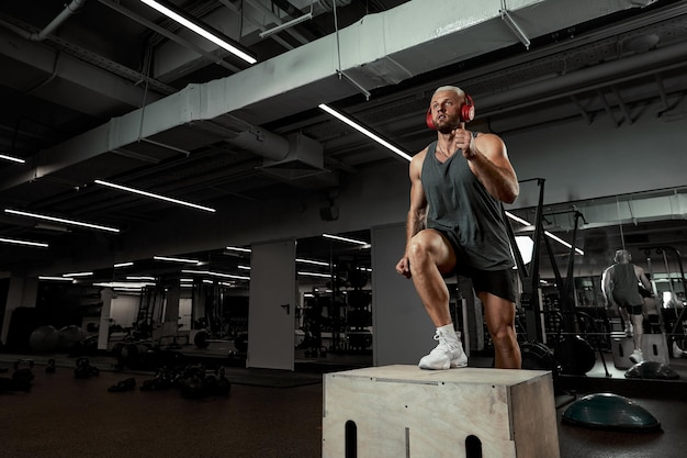Sexy muscular men using the platform for his legs on a dark colorful background of gym.