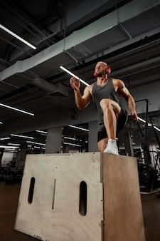 체육관의 어둡고 화려한 배경에서 다리를 위한 플랫폼을 사용하는 섹시한 근육질의 남자.
