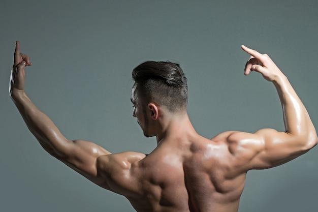 벌거 벗은 몸통을 가진 섹시한 근육질 남자 회색 표면에 스튜디오에서 제기 손으로 근육 몸통과 근육질의 남자
