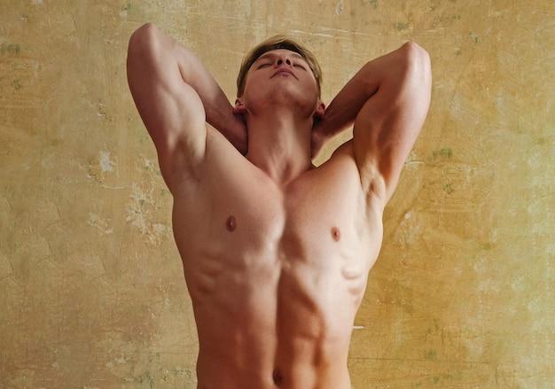 벌거 벗은 몸통이 강한 벗은 몸통 가슴 6 팩으로 포즈를 취하는 섹시한 근육질 남성