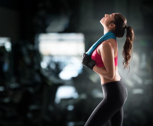 ジムタオルでトレーニングした後のセクシーな筋肉の女性