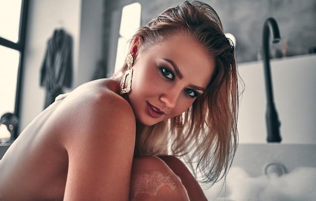 Сексуальная обнаженная женщина позирует в белой ванне, наслаждаясь расслаблением и греясь в пушистой пене.