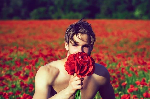 セクシーな裸の若い男は赤いポピーの花の花束を保持します