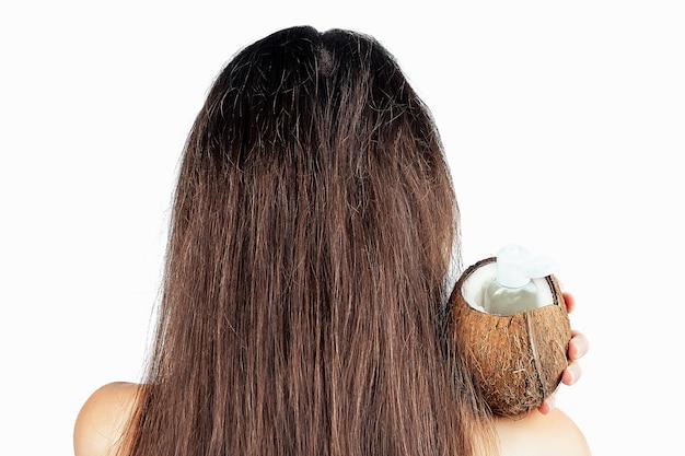 섹시한 누드 인도 여성이 병과 모자에서 코코넛 오일을 손에 든 어두운 갈색 머리의 긴 머리에 흰색을 격리합니다.