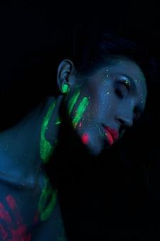 ネオンの光でセクシーなヌードの女性、女性の顔と体にuvペイント。完璧な姿と女性の胸、美しい髪