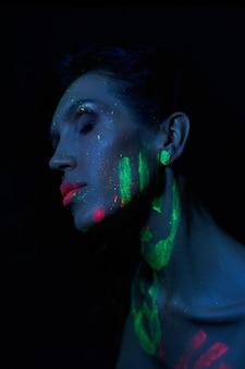 ネオンの光でセクシーなヌードの女性、女性の顔と体にuvペイント