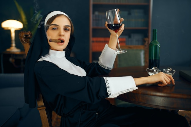 Sexy nun in a cassock smokes cigare and drinks wine, vicious desires. corrupt sister in the monastery, religion and faith, sinful religious people, attractive sinner