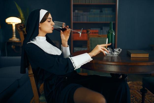 タバコとグラスワイン、悪意のある欲望と堕落したポーズで座っているカソックのセクシーな修道女。修道院の堕落した姉妹、宗教と信仰、罪深い宗教の人々、魅力的な罪人