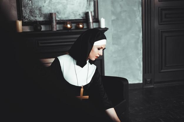 섹시한 수녀가 실내에서기도합니다. 아름다운 젊은 거룩한 자매. 검은 인테리어에 가운에 십자가와 젊은 아름 다운 수녀.